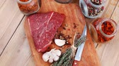 raw beef meat fillet with peppercorn and thyme and differnt spices in glass bottles ready to grill on wood figured aged board over table 1920x1080 intro motion slow hidef hd Stock Footage