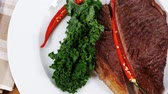 single roast : grilled beef steak fillet meat with red hot pepper and raw kale leaf with ketchup sauce served plate over wood table 1920x1080 intro motion slow hidef hd Stock Footage