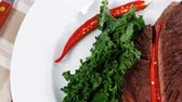 grilled beef steak fillet meat with red hot pepper and raw kale leaf with ketchup sauce served plate over wood table 1920x1080 intro motion slow hidef hd Stock Footage