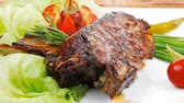 meat plate on wooden table: roast ribs with tomatoes and red hot peppers 1920x1080 intro motion slow hidef hd