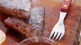 fresh beef meat steak with red hot pepper and bun slices served on plate with whiskey on wood over table with cutlery 1920x1080 intro motion slow hidef hd Stock Footage
