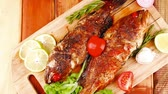 seabass : healthy food: two fried sea bass fish served with tomatoes and vegetables on big wooden board over table 1920x1080 intro motion slow hidef hd Stock Footage