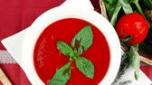 guardanapo : cold fresh diet tomato soup with basil thyme and dry pepper in big bowl over red mat on wood table ready to eat 1920x1080 intro motion slow hidef hd