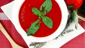 bazylia : cold fresh diet tomato soup with basil thyme and dry pepper in big bowl over red mat on wood table ready to eat 1920x1080 intro motion slow hidef hd