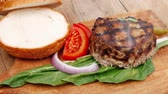 queijo cheddar : extra thick hot beef meat hamburger lunch on wooden plate with tomatoes and salad over wooden table with cutlery and fresh sweet bun 1920x1080 intro motion slow hidef hd Vídeos