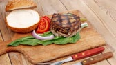 extra thick hot beef meat hamburger lunch on wooden plate with tomatoes and salad over wooden table with cutlery and fresh sweet bun 1920x1080 intro motion slow hidef hd Stock Footage