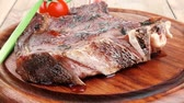 served main course: grilled pork ribs served with green chives and cherry tomato on wooden plate Stock Footage