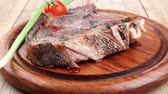 アントレ : served main course: grilled pork ribs served with green chives and cherry tomato on wooden plate 動画素材