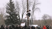 торжества : Gomel, Belarus. Young Man Climbs On A Wooden Post On Traditional Holiday Dedicated To Approach Of Spring - Slavic Celebration Shrovetide. National Traditional Holiday Maslenitsa