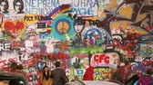 praga : Prague, Czech Republic. People walking and taking photo in famous place in Prague - The John Lennon Wall. Wall filled with Lennon inspired graffiti and lyrics from Beatles songs Stock Footage