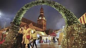 riga : Riga, Latvia - December 18, 2017: People Walking Near Traditional Christmas Market On Dome Square With Riga Dome Cathedral. Famous Landmark In Winter Evening In Festive Illuminations Lighting Stock Footage