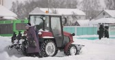 条件 : Tractor Cleaning Snow In Winter Snowy Day In City. Winter Service Vehicle In Work. Snow Removal Vehicle