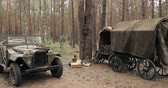 urss : Russian Soviet World War II Four-wheel Drive Army Truck Gaz-67 Car And Peasant Carts In Forest. WWII Equipment Of Red Army