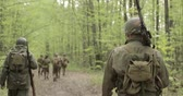 druhé světové války : American Soldiers Of USA Infantry Of World War II Marching Walking Along Forest Road In Summer Day. Group of Soldiers Marching In Forest. Dostupné videozáznamy