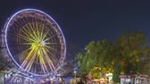 Rotating In Motion Illuminated Attraction Ferris Wheel And Brightly Carousel Merry-Go-Round On Summer Evening In City Amusement Park Wideo