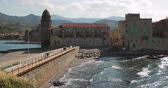 Collioure, France. People Tourists Walking In Coast Near Church Of Our Lady Of The Angels Across The Bay In Sunny Spring Day