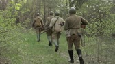 urss : Russian Soviet Infantry Red Army Soldiers Of World War II Marching Walking Along Forest Road In Summer Day. Group of Soldiers Marching In Forest