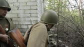 szovjet : Gomel, Belarus - April 30, 2018: Russian Soldiers Of World War II Performing Mopping-up Operation. Red Army Infantry Cover Each Other During House Assault. Men Attacking During Historical Reenactment
