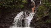 falésias : Woman jumping in a pool below a waterfall Vídeos
