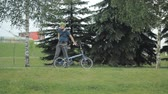 grizzled : Man on bicycle riding to the park with laptop Stock Footage