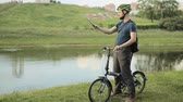 grizzled : Man on folding bicycle with smartphone Stock Footage