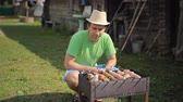 brother : Man prepares meat on the fire. Twists meat over a fire in the garden Stock Footage