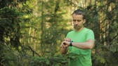 yenilik : A man walks through the forest with smart watch and looking at the navigation application. He chooses the right direction Stok Video