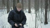 breath vapor : A young man in winter forest freeze. Hes breathing on his hands, rubs and wears a hat and gloves. Snowy landscape. Stock Footage
