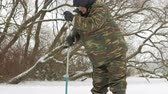 smelt : Winter fishing on river. A man drills a hole in ice.