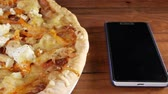 doba jídla : The mobile phone rests on a wooden table next to a homemade pizza with different cheeses and tomato. Moving camera
