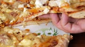 different cheeses : A mans hand takes a piece of homemade pizza with different cheeses and tomato. Moving camera