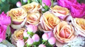 Spraying of beautiful bouquet of bright pink and beige roses.