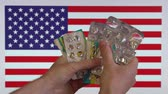 tabletler : A man holds a empty blister packs, United States flag visible on the background.