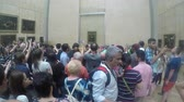 anêmona : Shot of People stand in line to watch the Mona Lisa from close