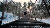 distribuidor : Novice blogger filming himself using a smartphone and a device to stabilize the video. Stylishly dressed man climbs down the steps in the forest. Vídeos