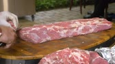 cielęcina : Cook in white gloves cuts off pieces of steaks from a large piece of raw meat. Quality pork tenderloin for the preparation of delicious dishes. Sharp knife and a wooden board. Meat processing before preparation. Wideo