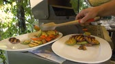receitas : Cook lay out on plates with help of forceps various vegetables such as eggplant, pepper, zucchini and mushrooms. Healthy food is cooked on the grill. Man is preparing to serve a deliciously cooked dish.