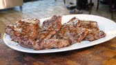 Fried meat lies on a white plate and emits steam. Ready meat steaks are sprinkled with salt before serving. Restaurant dishes before consumption