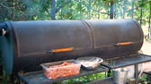 Cooking of meat dishes outdoors. Large black outer grill from which smoke comes. Equipment for frying a large number of steaks and sausages.