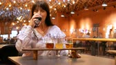 Adult woman tastes several types of beer in small glasses on a wooden stand. The taster did not like the drink very much. Preparation for the festival of beer. Stok Video
