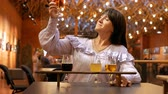 Professional beer taster tries several types of drinks and is pleased with the result. An adult beautiful woman drinks from large glasses and smiles. Stok Video