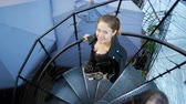 Beautiful young woman goes down the spiral staircase and cute looks up. A feminine neckline is a top view.