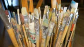 A lot of different paint brushes stand upright in vases. Professional equipment of the artist. Art Studio. Focus of the camera moves by objects.