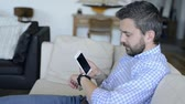 telefone : Man sitting on sofa using smartphone and smart watch
