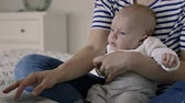 working parents : Unrecognizable mother with baby son, sitting on bed, working Stock Footage