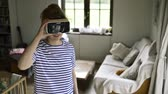 kurtyna : Woman wearing virtual reality goggles standing in living room