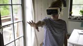 cortina : Woman wearing virtual reality goggles standing in a kitchen Stock Footage