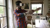 cortina : Man wearing virtual reality goggles standing in a kitchen