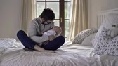 cortina : Father holding his baby boy, sitting on a bed Stock Footage