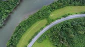 curva : Aerial view of highway, river, forest and grassland